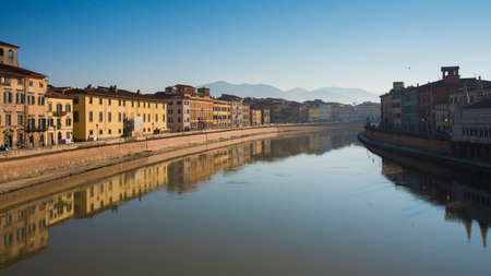 Colorful old houses with reflection in a river at Pisa, Tuscany, Italy, Europe.