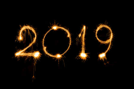 Happy new year 2019 written with sparkle fireworks on isolated black background Imagens