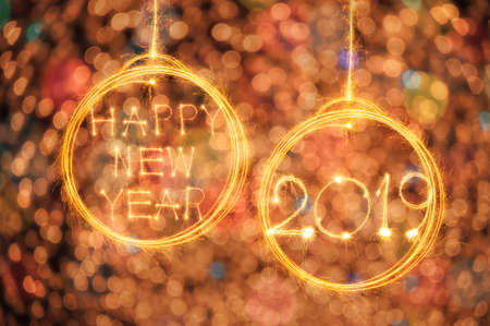Hang Happy new year text in ball and 2019 written with sparkle fireworks on gold bokeh background