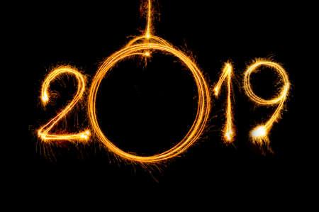 Cuelgue el texto de Feliz año nuevo en bola y 2019 escrito con fuegos artificiales brillantes sobre fondo dorado bokeh