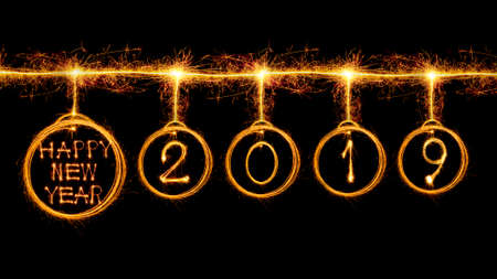 Happy new year 2019 text and circle look like bulb written with sparkle fireworks isolated on black background Banco de Imagens