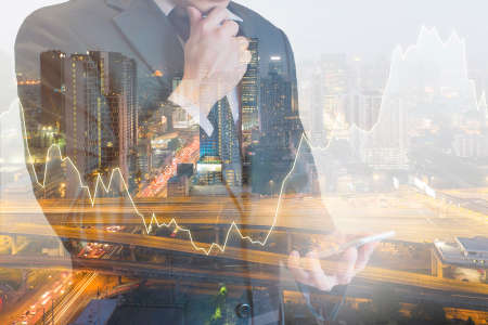 Double exposure of professional businessman looking smart phone with cityscape and financial / trading graph in Business trading and technology concept