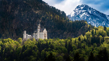 The famous Neuschwanstein castle with snow mountain background, Germany 스톡 콘텐츠