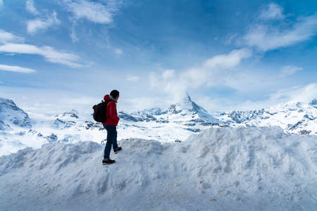 Man in red jacket is looking Matterhorn peak on Gornergrat peak, Zermatt, Switzerland