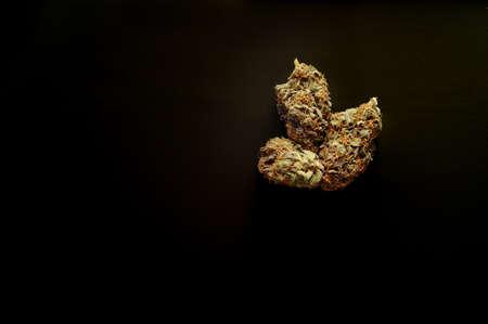 Marijuana buds closeup. Medicinal cannabis flowering on black background. Hemp recreation, medical usage, legalization. Stock Photo