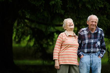 Gelukkig hoger paar kijken naar de camera en lachen, Senior vrouw knuffelen haar partner op een zonnige dag, Lachend blanke ouder echtpaar omarmen Stockfoto