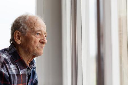 Ritratto di uomo anziano che osserva fuori finestra Archivio Fotografico