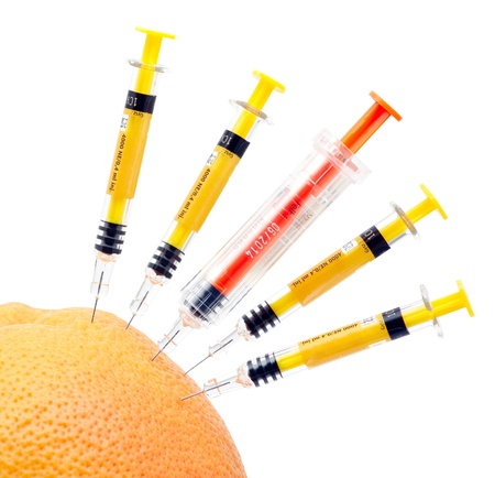 Syringes and orange on white background. Stock Photo - 12685047