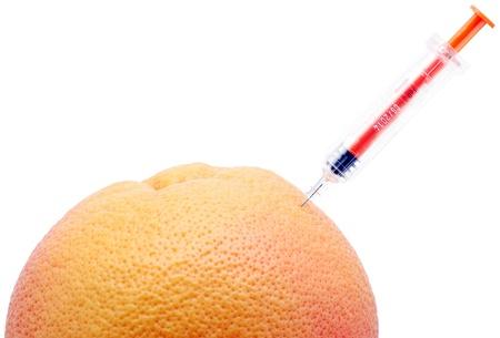 chemical peels: Syringe and orange on white background.