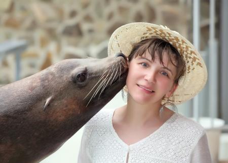 cara leon: Mujer joven besando a una junta en el zoo. Foto de archivo