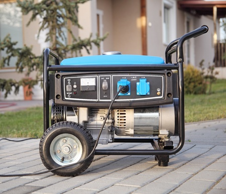 potency: Gasoline powered portable generator at home. Stock Photo