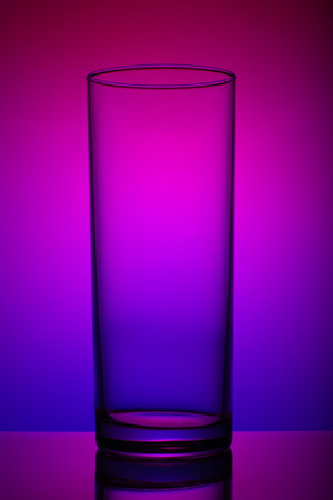 Transparent glass cup, shot in the light, with a vignette, on a multi-colored background. art, subject, advertising.