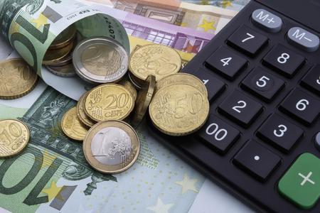eur: Euro (EUR) notes, coins, and a calculator. Business concept. Stock Photo