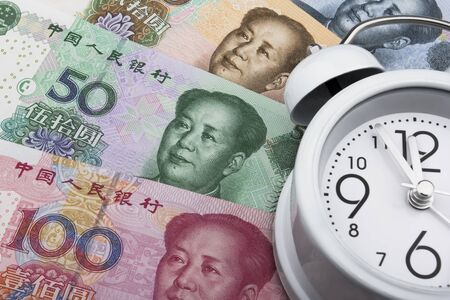 rmb: Chinese money (RMB) and clock. 100, 50, 20 and 10 RMB note. Time is money. Business concept