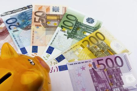 eur: Piggy bank looking at Euro (EUR) notes.