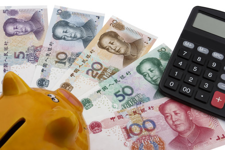 calculator chinese: Chinese money (RMB), 100, 50, 20, 10 and 5 RMB note underneath a piggy bank and a calculator. Business concept.