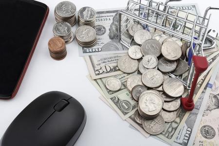 carretilla de mano: Carro de compras con las monedas billetes en un smartphone y un ratón.