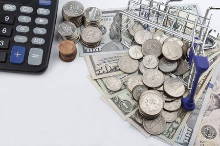 carretilla de mano: Carro de compras con las monedas de espacio de la copia en d�lares estadounidenses, billetes, y una calculadora. Foto de archivo