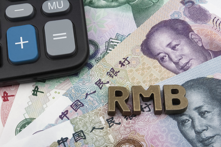 calculator chinese: Chinese Yuan (CNYRMB) banknotes with the letters RMB on top, and a calculator in the left top corner. Stock Photo