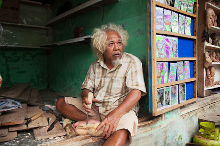 trinchante: BUKIT LAWANG, SUMATRA, INDONESIA - AUGUST 15,2012: Wood carver produces decorative mask in his workshop