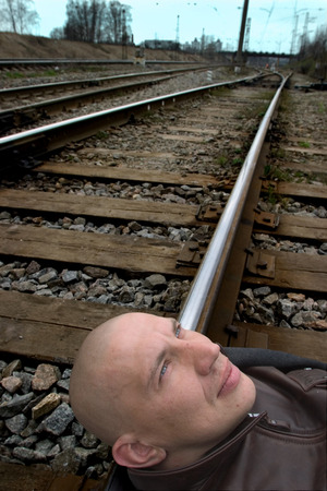 unwillingness: MOSCOW, RUSSIA - AUGUST 20.2015: bald  man lying on the rails