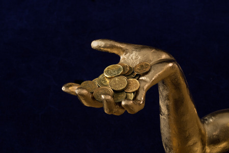 a handful of coins in gold-plated hand