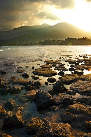 sunset over the mountains and low tide on the island of Tioman Stock Photo