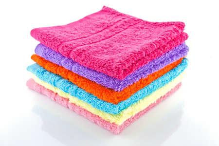 orange washcloth: stacked colorful towels on a white background Stock Photo