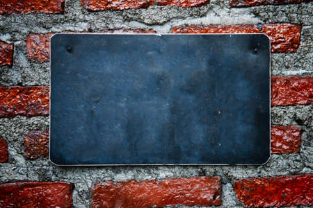 blank chalkboard hanging on brick wall