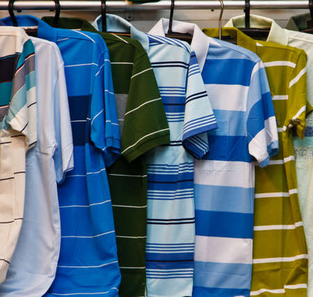 Colors of rainbow  Variety of casual shirts on wooden hangers photo