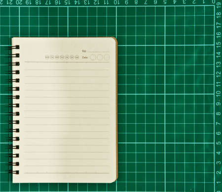 Open blank notebook on a cutting mat   photo