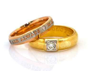 Gold wedding rings engraved on white isolated