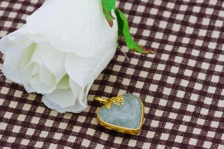 jade: jade jewelry with white rose on background Stock Photo