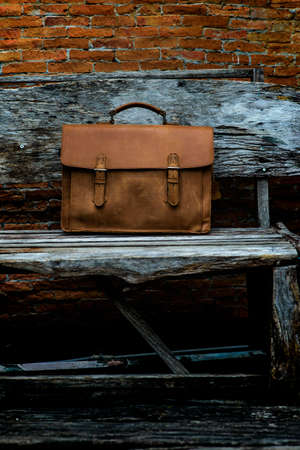 duffel: Brown Leather laptop bag corporate  on old woden chair Stock Photo