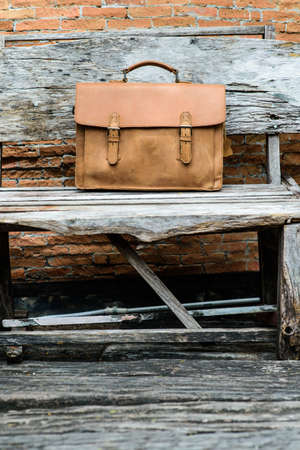 duffel: Brown Leather laptop bag corporate  on old woden chair Archivio Fotografico