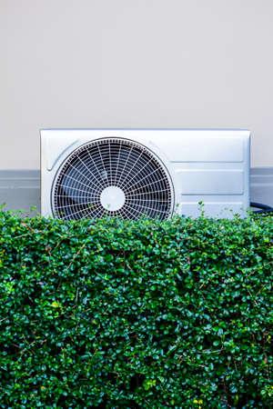 compresor: compresor de aire en la pared con el �rbol verde