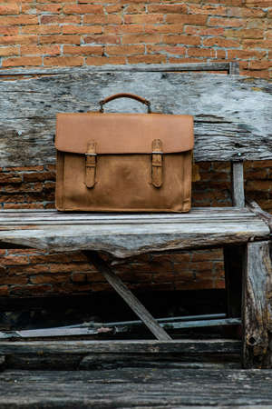 woden: Brown Leather laptop bag corporate  on old woden chair Stock Photo