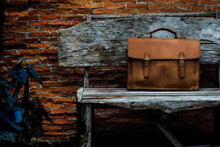 Bruin lederen laptoptas ondernemen op oude woden stoel Stockfoto