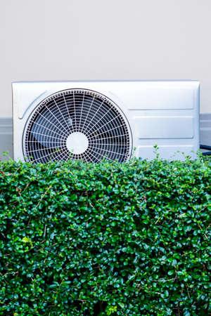 compresor: compresor de aire en la pared con el árbol verde