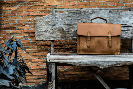 Brown Leather laptop bag corporate  on old woden chair Stock Photo