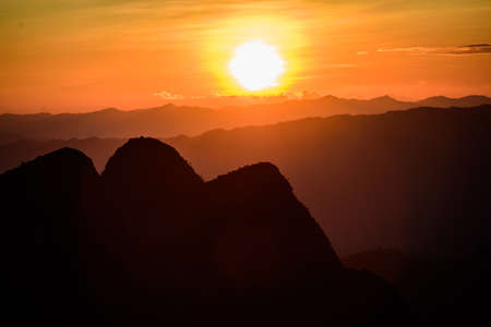 faintly visible: Sun setting over hills in Thailand