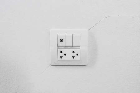 Electrical outlet with plug on white painted wall photo