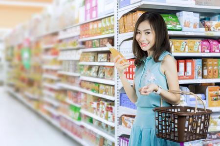 スーパーでフルーツ ジュースを購入する若い女性