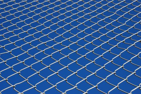 Chain link fence against a bright blue sky, looking up photo