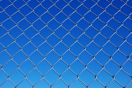 Chain link fence with background sky from light to dark blue sky