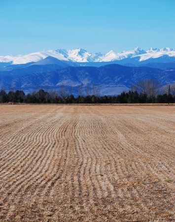 A ploughed field near Boulder, Colorado, near snowcapped Rocky Mountains in winter after harvest