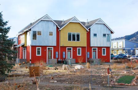 commune: New condominiums, brightly painted in modern colors, share a rustic garden and play area Stock Photo