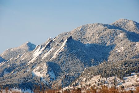 glisten: Morning after a snow storm, the scenic Flatirons mountains shine above Boulder, Colorado