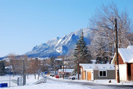 blanketed: Scenic snow-covered mountain towers above a peaceful suburban area by a city park