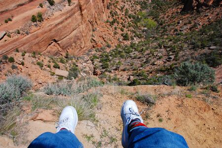 foreshortening: Dangling feet far above the bottom of Ute Canyon in Colorado National Monument Stock Photo